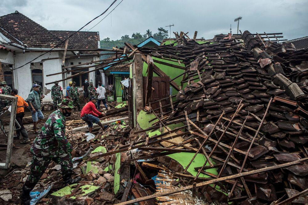 Soldados e residentes indonésios checam casas destruídas pelo terremoto em Malang, na ilha de Java, 11 de abril de 2021