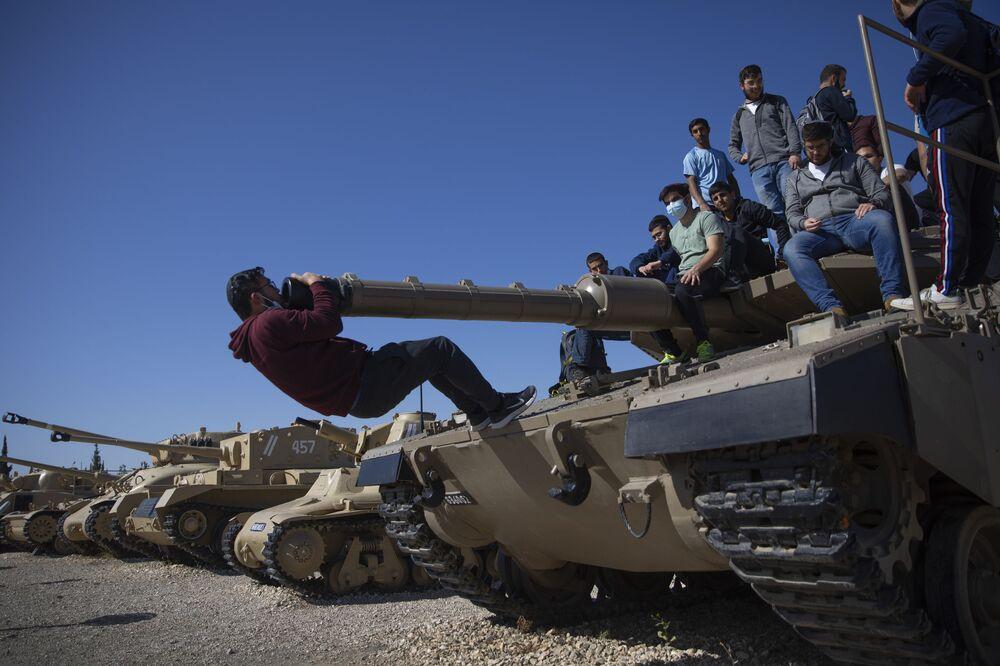 Estudantes sobre um tanque em Israel durante a cerimônia anual do Dia de Memória em homenagem aos soldados falecidos e vítimas do terrorismo, Israel, 14 de abril de 2021