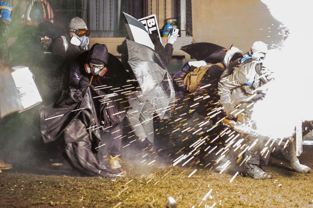 Manifestantes se escondem de munições antimotim disparadas pela polícia durante protestos em Minnesota, 13 de abril de 2021