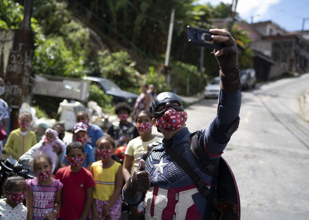Policial militar fantasiado de Capitão América tirando selfie com crianças em Petrópolis, Rio de Janeiro, 14 de abril de 2021