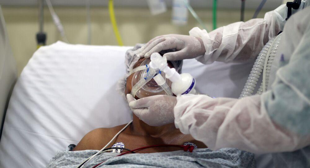 Em São Paulo, uma fisioterapeuta ajusta uma máscara de oxigênio em um paciente com COVID-19, em uma UTI do Hospital Municipal de Parelheiros, em 8 de abril de 2021