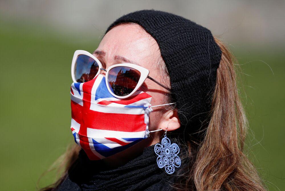 Uma mulher usando uma máscara no Castelo de Windsor durante o funeral do príncipe Philip