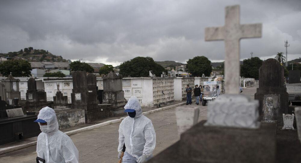 Trabalhadores com equipamento de proteção contra a COVID-19 caminham no cemitério de Inahuma, no Rio de Janeiro, em 15 de abril 2021