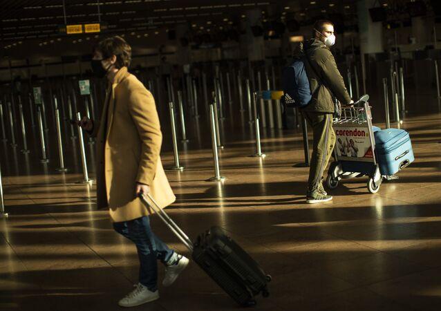 Viajantes, usando máscaras faciais contra COVID-19, caminham no Aeroporto Internacional de Bruxelas, na Bélgica, 22 de janeiro de 2021