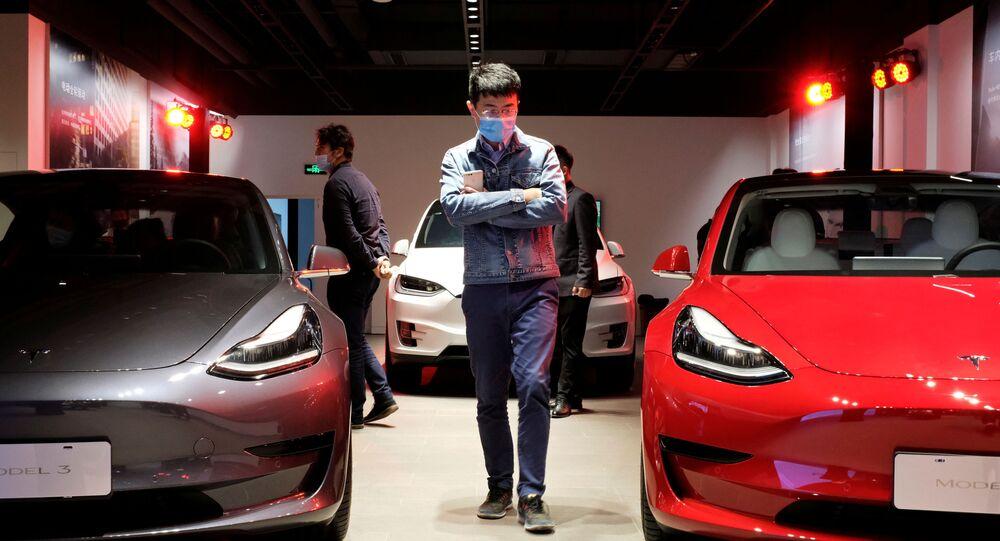 Homem observa carros Tesla Model 3 sedans e Tesla Model X esportivos em showroom da Tesla em Xangai, em maio de 2020