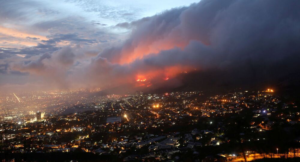 Chamas são vistas perto da cidade, alimentadas por ventos fortes, após um incêndio florestal nas encostas da Table Mountain na Cidade do Cabo, África do Sul, em 19 de abril de 2021.