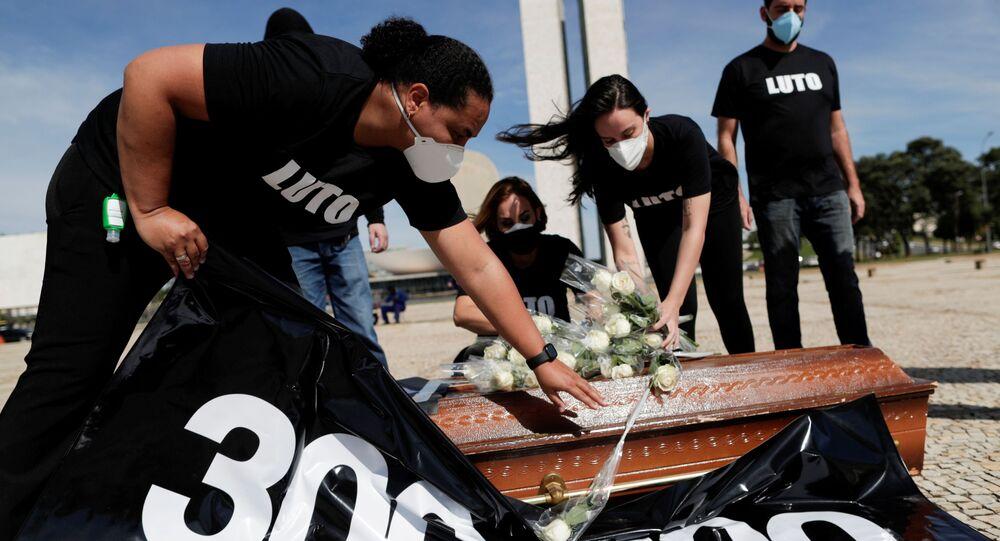 Profissionais de Saúde colocam flores em cima de um caixão para representar colegas mortos durante a pandemia, em protesto em Brasília, no Brasil, no dia 25 de março de 2021