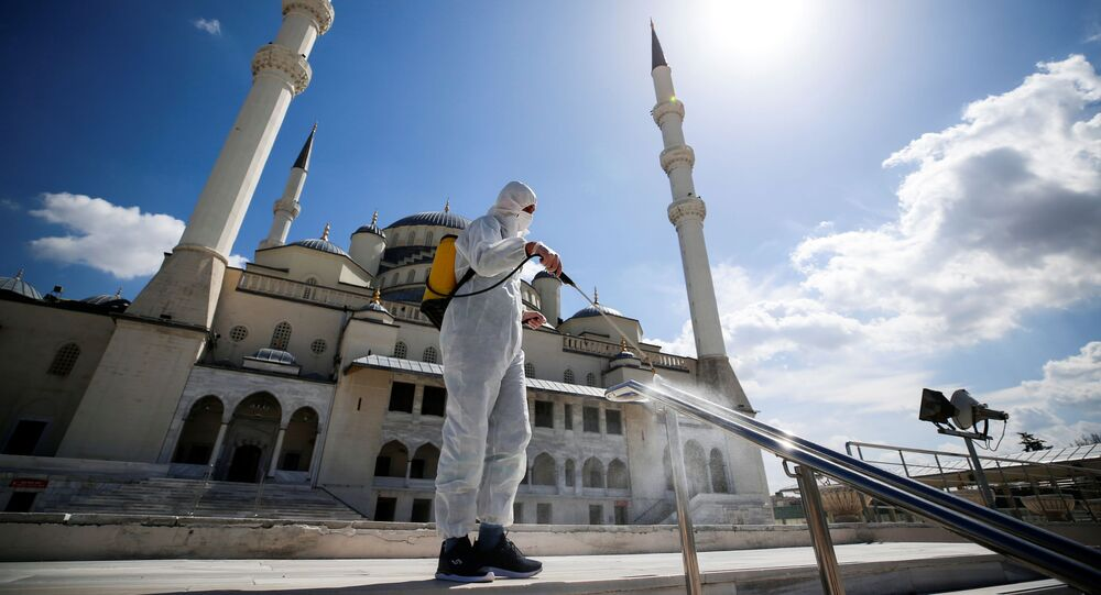 Em Ancara, um funcionário municipal higieniza uma praça em frente à mesquita de Kocatepe, em meio à pandemia da COVID-19, em 15 de abril de 2021
