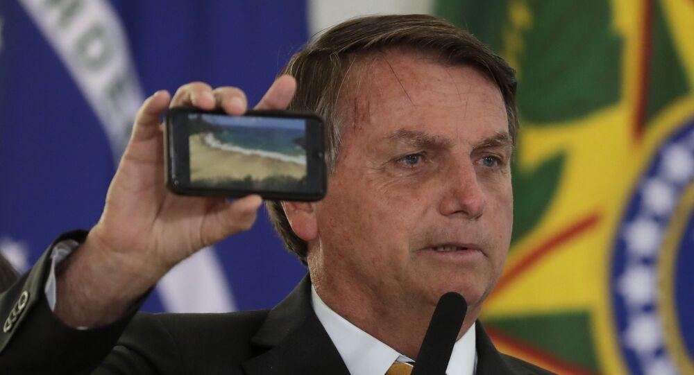 Jair Bolsonaro mostra a foto de uma praia durante cerimônia de apresentação de um programa para reiniciar o turismo, em meio à pandemia de COVID-19, em 11 de novembro de 2020