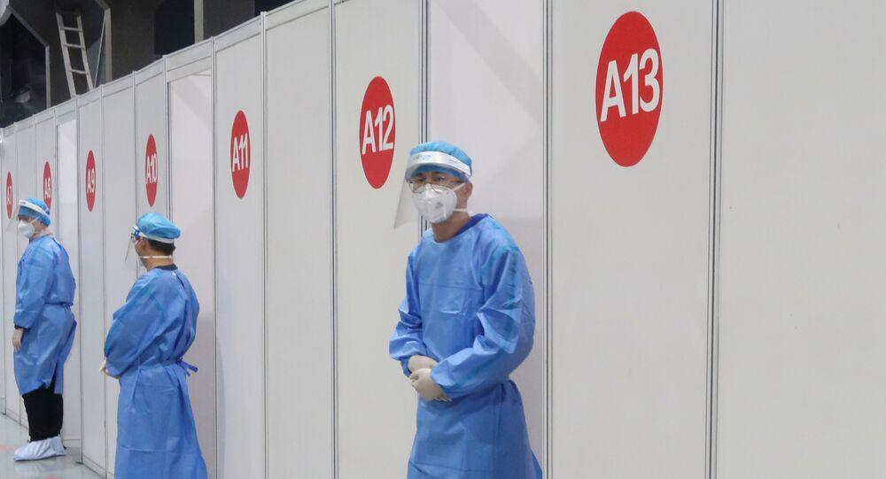 Agente da Saúde aguarda paciente para administrar vacina contra a COVID-19 em Pequim, China, 15 de abril de 2021
