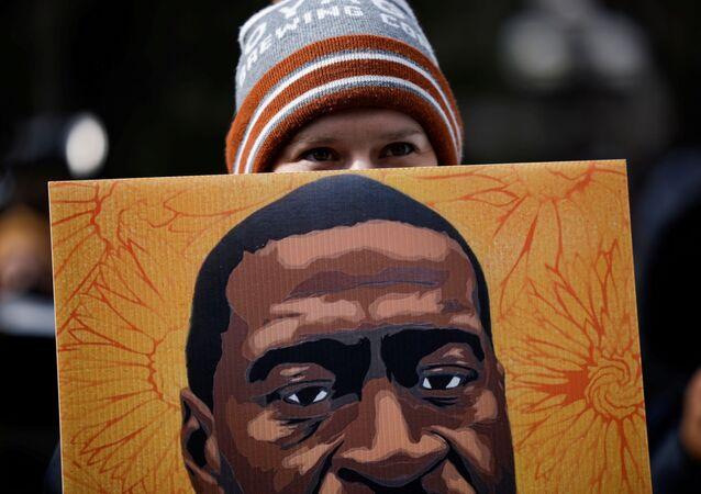 Manifestante segura cartaz com o rosto de George Floyd em Minneapolis, Minnesota, EUA, 20 de abril de 2021