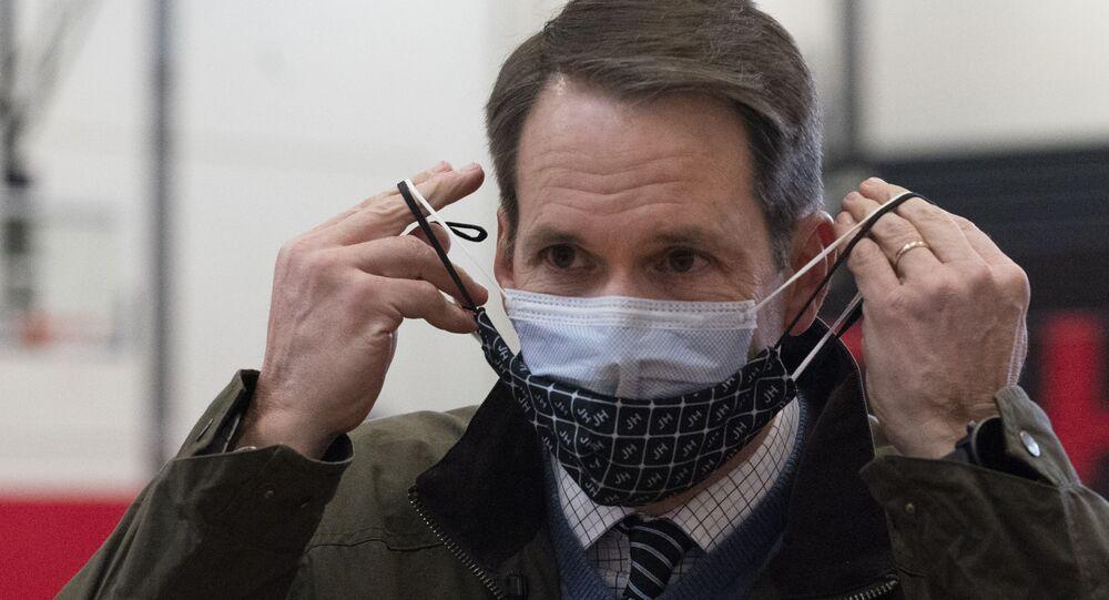 Congressista democrata norte-americano Jim Himes, de Connecticut, ajusta suas duas máscaras durante visita a clínica de vacinação no Centro de Ensino Médio de Bridgeport, Connecticut, EUA
