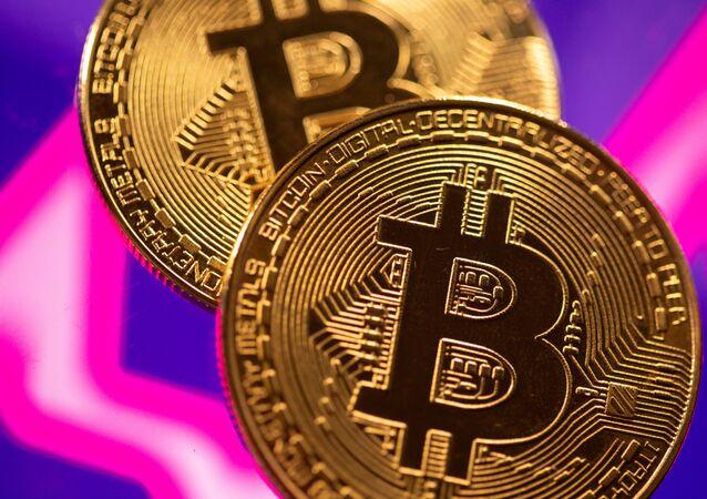 Representação da moeda virtual bitcoin em frente a um gráfico de ações de 15 de março de 2021