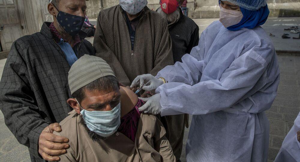 Na Caxemira, um homem indiano é vacinado contra a COVID-19 em meio à explosão de casos da doença no país, em 21 de abril de 2021