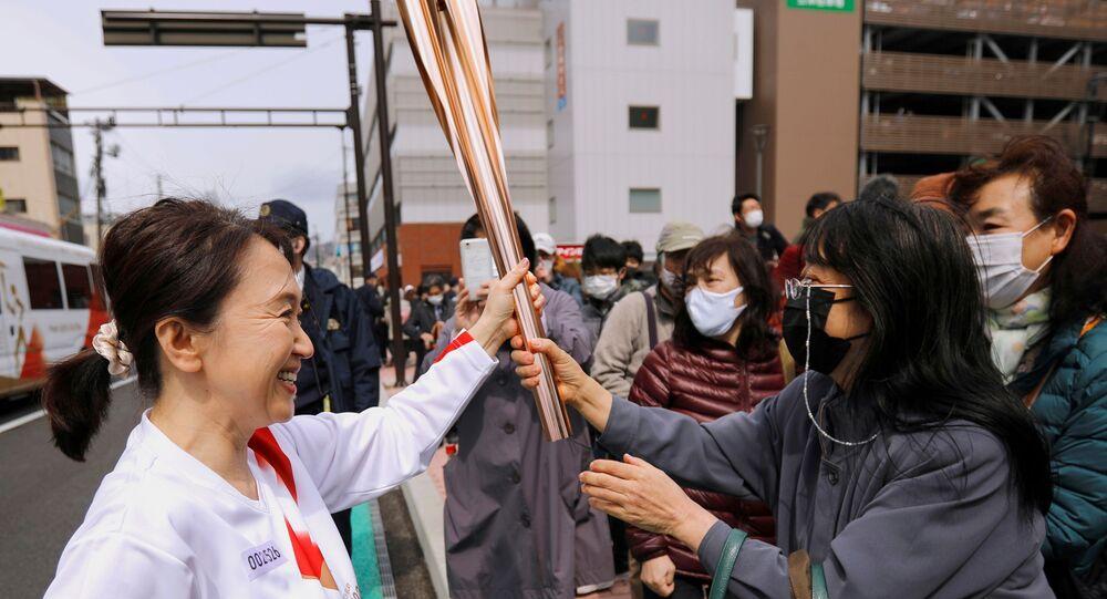 Espectadores admiram a tocha olímpica durante o segundo dia de revezamento em Fukushima, no Japão, em 26 de março de 2021