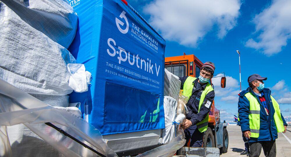 Trabalhadores transportam um carregamento da vacina russa Sputnik V, no Aeroporto Internacional de Manas, em Bishkek, Quirguistão.