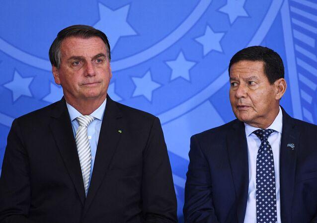 O presidente Jair Bolsonaro ao lado do vice-presidente Hamilton Mourão durante cerimônia em Brasília.