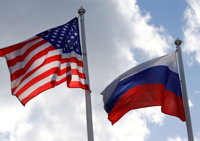 Bandeiras da Rússia e dos EUA hasteadas perto de uma fábrica em Vsevolozhsk, Rússia, 27 de março de 2019