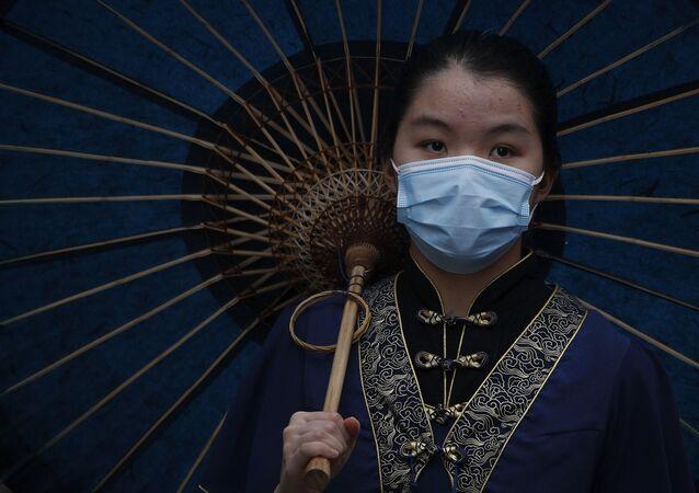 Uma mulher vestida com um traje tradicional usa uma máscara protetora para ajudar a conter a disseminação do novo coronavírus visita o popular ponto turístico de Nanluonguxiang depois de reaberto para turistas após o surto de coronavírus em Pequim, domingo, 3 de maio de 2020