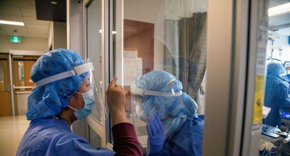 Enfermeiras comunicam através da porta de vidro da sala de isolamento de um paciente com COVID-19 internado na unidade de terapia intensiva em Toronto, Canadá, 15 de abril de 2021