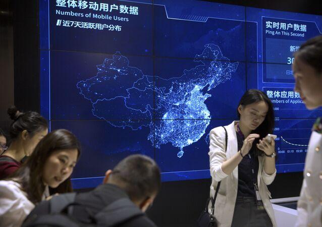 Os visitantes usam seus smartphones em frente a uma tela que mostra usuários de telefones celulares na China em um estande para a empresa de tecnologia chinesa Ping'an Technology na Global Mobile Internet Conference (GMIC) em Pequim, 26 de abril de 2018