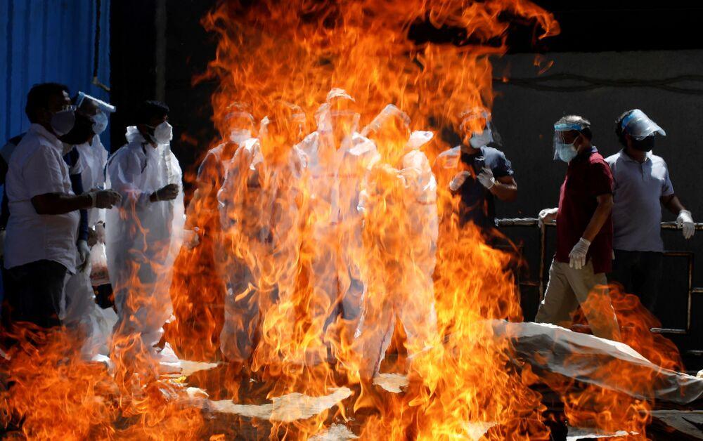 Familiares usando equipamento de proteção individual assistem ao funeral de um homem que morreu da COVID-19 em um crematório de Nova Deli, Índia, 21 de abril de 2021