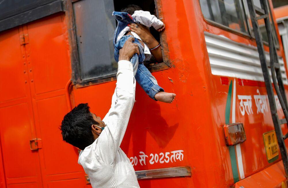 Trabalhador migrante passa seu filho através de janela de ônibus no regresso a seu povoado, após o governo de Deli ter anunciado o confinamento de seis dias para parar a propagação da COVID-19, em Gaziabade, arredores de Nova Deli, Índia, 20 de abril de 2021