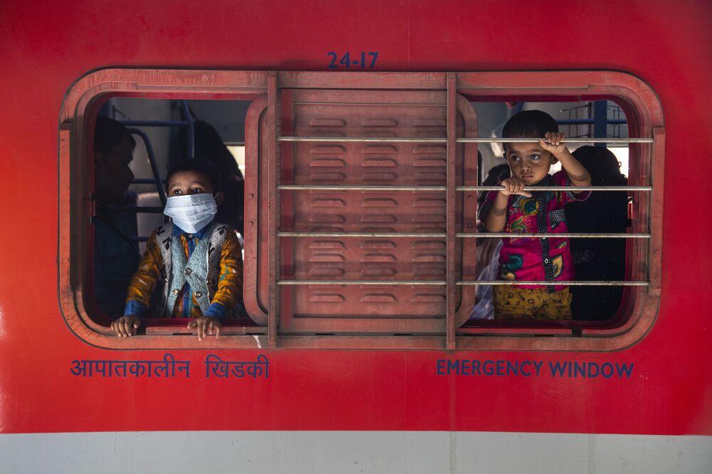 Meninos olham pela janela de trem na estação ferroviária em Guwahati, Índia, 19 de abril de 2021