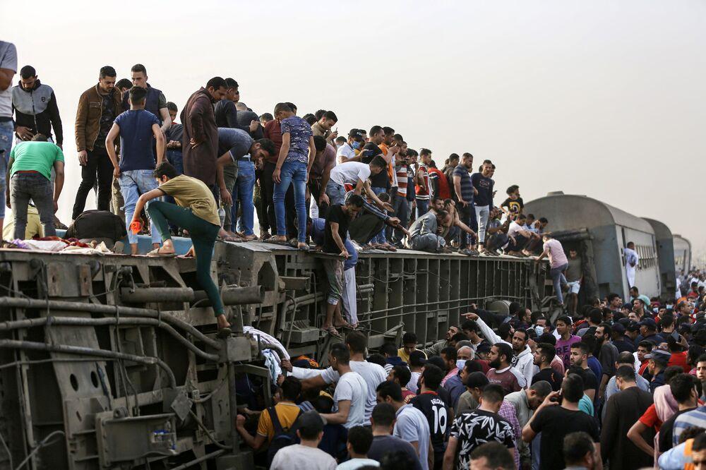 Pessoas sobem em carruagem de trem virada após o acidente na cidade de Toukh, Egito, 19 de abril de 2021. O trem descarrilou, deixando 11 pessoas mortas e 98 feridas