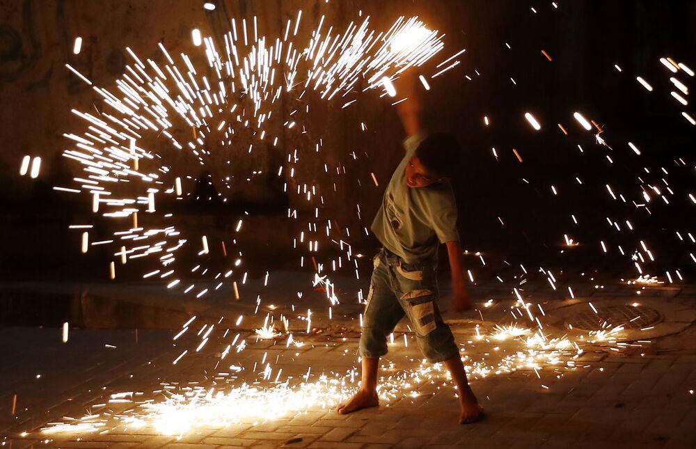 Menino joga com fogos de artifício celebrando o Ramadã, o mês de jejum dos muçulmanos, na cidade de Gaza, Palestina, 20 de abril de 2021