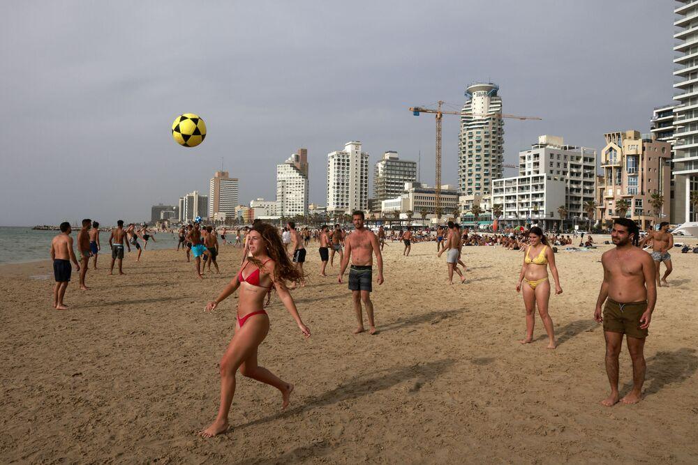 Pessoas jogam futebol na praia de Tel Aviv, Israel, 19 de abril de 2021, após o governo ter anunciado que não é mais necessário usar máscaras no exterior