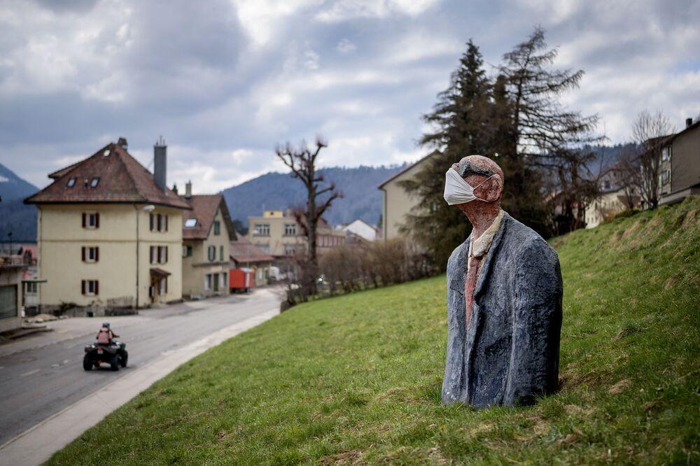Estátua de homem usando máscara de proteção em Sainte-Croix, Suíça, 18 de abril de 2021