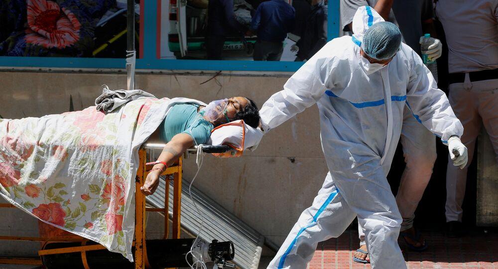 Em Nova Deli, na Índia, um profissional de saúde move uma paciente de COVID-19 em meio ao pico da pandemia no país, em 24 de abril de 2021