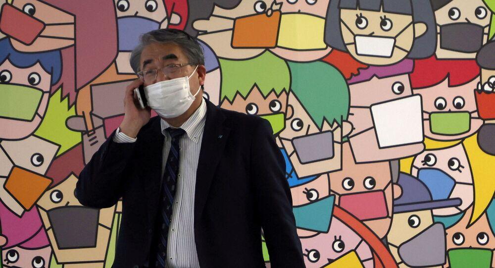 Pedestre passa em frente a muro com arte sobre a COVID-19, em Tóquio, no Japão, no dia 16 de abril de 2021