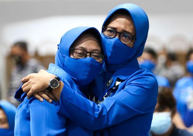 Familiares de tripulantes do submarino KRI Nanggala-402 se abraçam