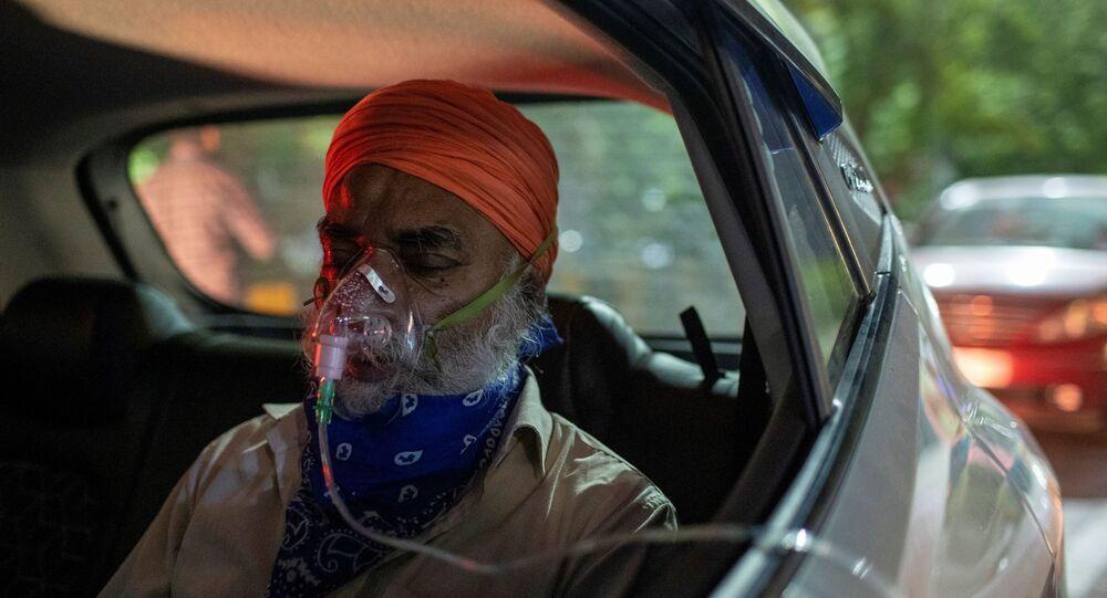 Em Ghaziabad, na Índia, um homem com problemas respiratórios recebe oxigênio dentre de um carro em meio ao pico da COVID-19 no país, em 24 abril de 2021
