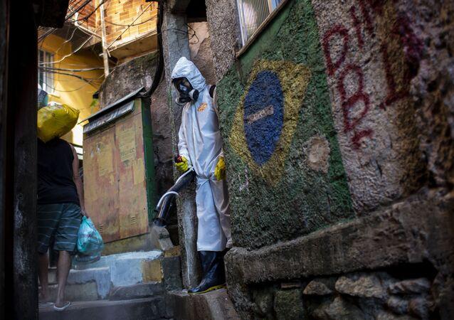 Funcionário pulveriza desinfetante em um beco para ajudar a conter a propagação do novo coronavírus na favela Santa Marta, no Rio de Janeiro, em 24 de abril de 2021.