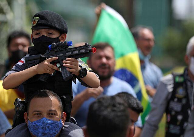 Garoto aponta arma de brinquedo durante protesto contra o presidente Jair Bolsonaro, em Manaus, 23 de abril de 2021