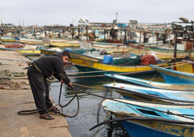 Um pescador palestino amarra um barco após Israel restringir a zona de pesca palestina em resposta aos foguetes palestinos, no porto da Cidade de Gaza em 26 de abril de 2021