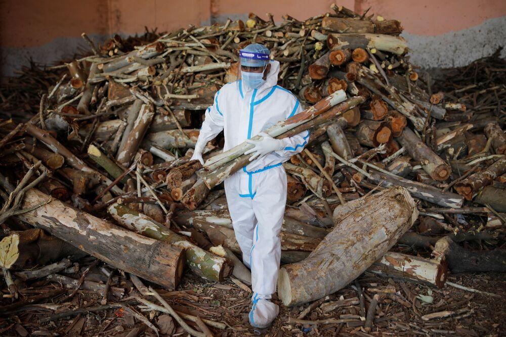 Em Nova Deli, na Índia, um homem carrega madeira para preparar piras funerárias em meio em um crematório para corpos de pacientes infectados com a COVID-19, em 26 de abril de 2021