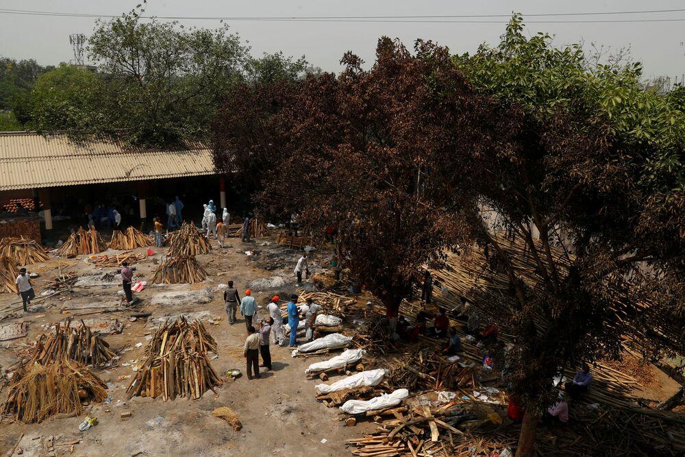 Em Nova Deli, na Índia, pessoas preparam piras funerárias para a cremação em massa de corpos de pacientes infectados com a COVID-19, em 26 de abril de 2021