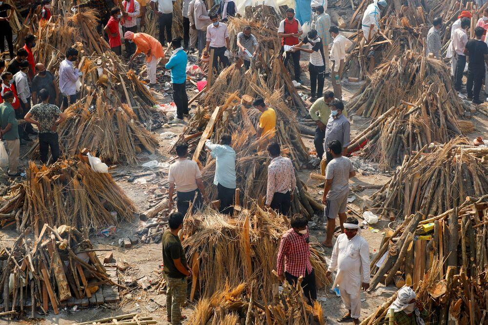 Em Nova Deli, na Índia, pessoas preparam piras funerárias para a cremação de corpos de pessoas infectadas com a COVID-19, em 26 de abril de 2021