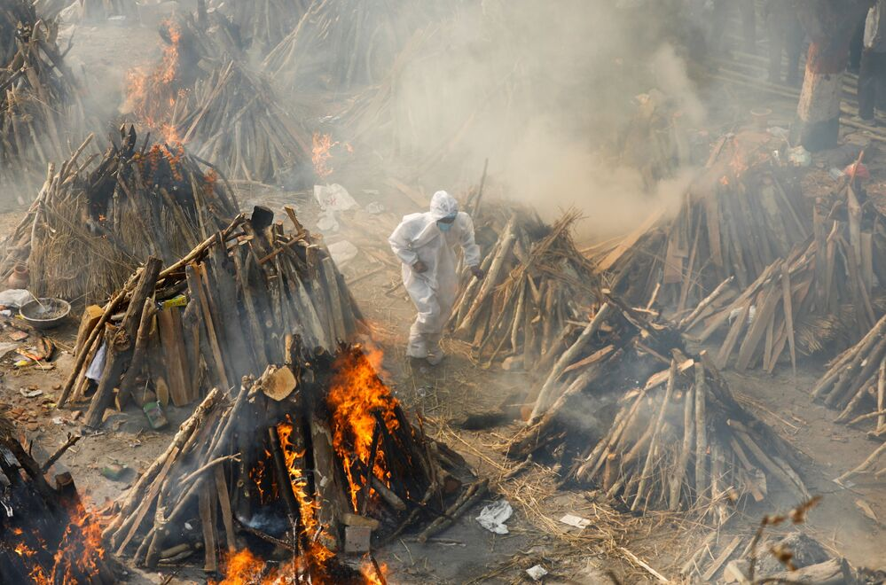 Em Nova Deli, na Índia, um homem corre em meio a piras funerárias de corpos de pessoas infectadas com a COVID-19, em 26 de abril de 2021