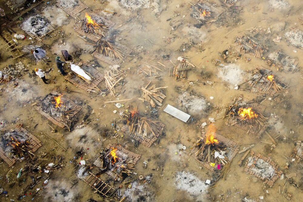 Em Nova Deli, na Índia, parentes e amigos participam da cremação de uma pessoa morta por COVID-19, em 26 de abril de 2021