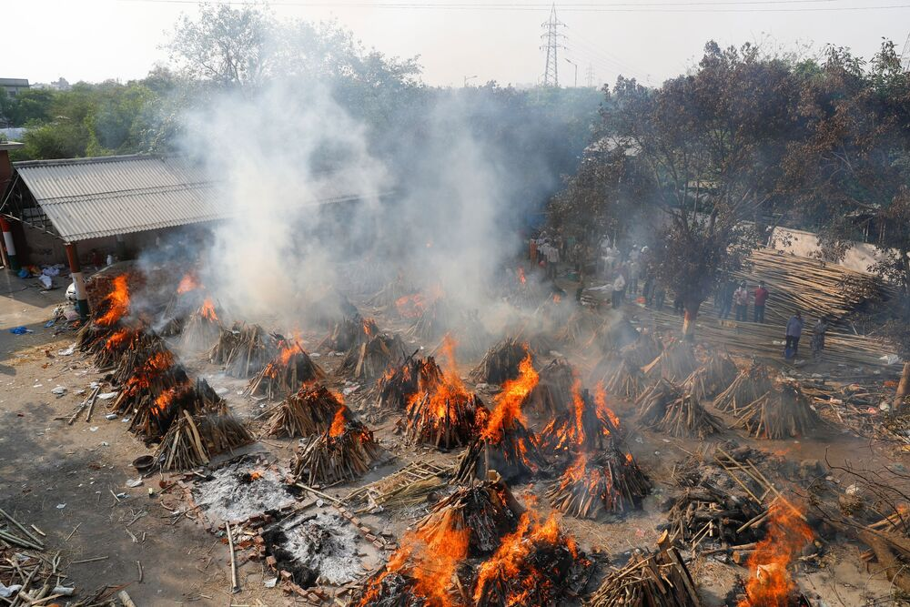 Em Nova Deli, na Índia, piras funerárias realizam a cremação de pessoas mortas por COVID-19, em 26 de abril de 2021