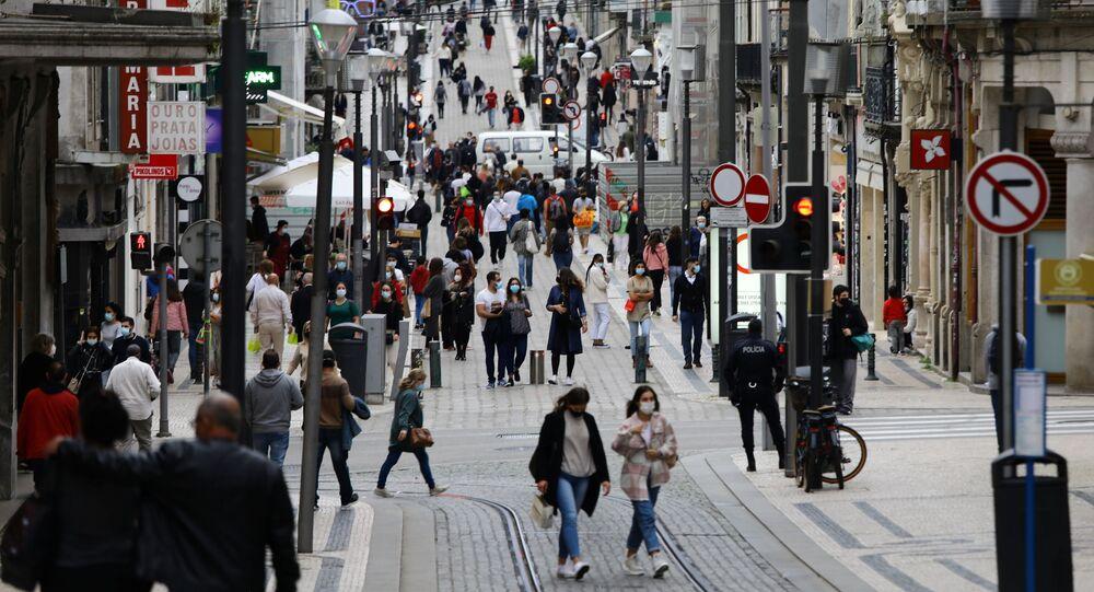 Na cidade do Porto, em Portugal, pessoas caminham nas ruas em dia de comércio aberto em meio à pandemia da COVID-19, em 19 de abril de 2021