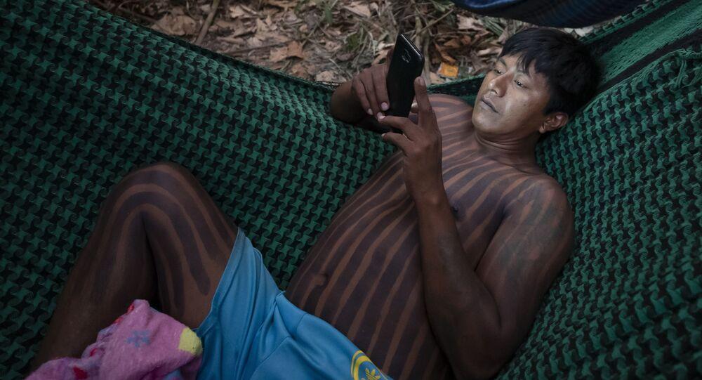 Indígena Kayapó checa seu celular enquanto descansava em uma rede perto de Novo Progresso, no estado do Pará, em setembro de 2019