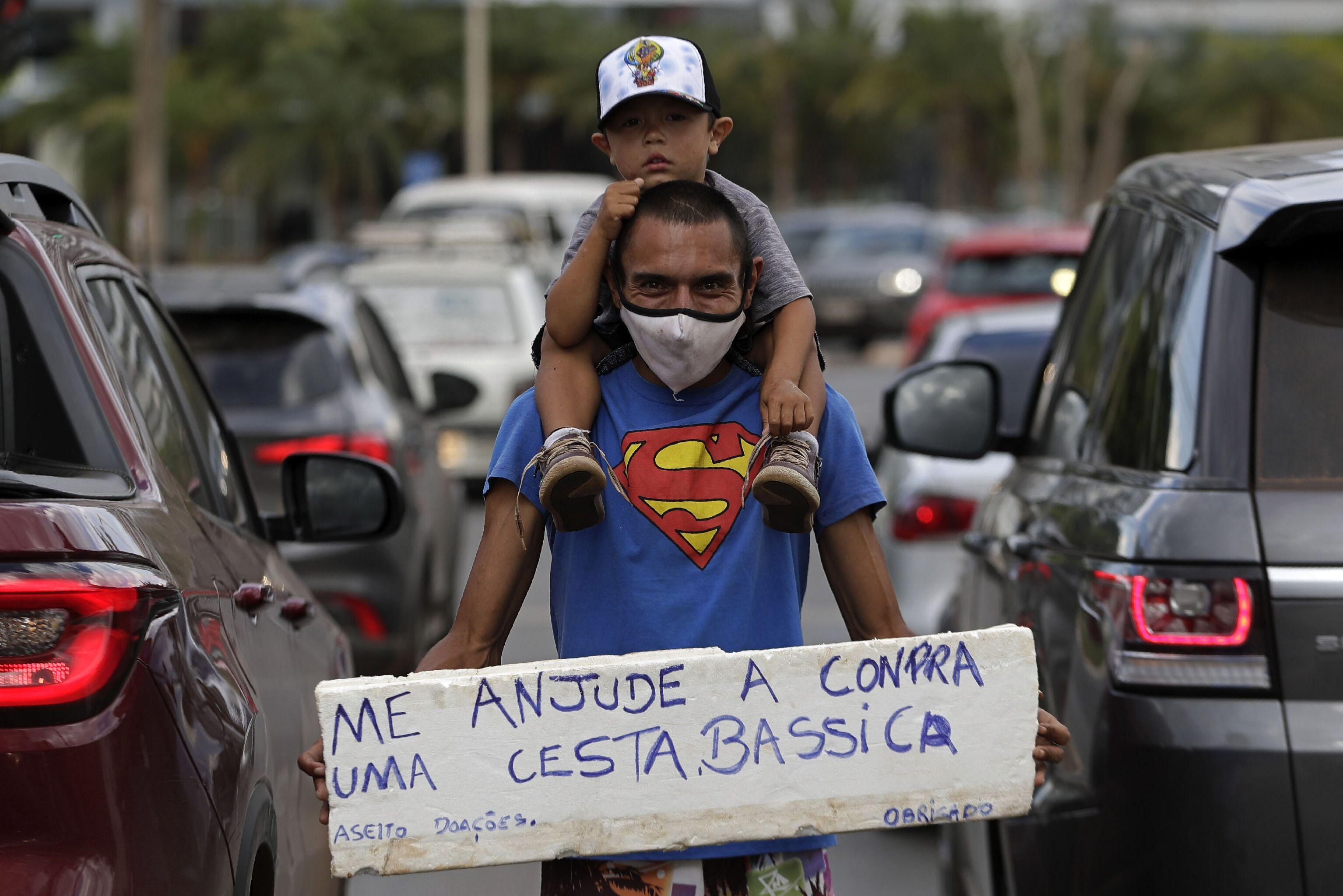 Homem acompanhado do seu filho pede ajuda para compra de alimentos em Brasília, 26 de abril de 2021