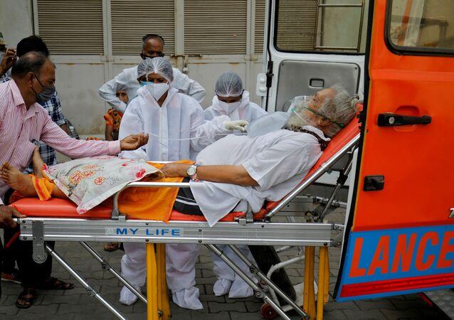 Um paciente com máscara de oxigênio é levado para dentro de um hospital COVID-19 para tratamento, em meio à disseminação da doença do coronavírus em Ahmedabad, Índia, dia 26 de abril de 2021
