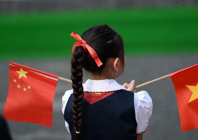 Garota segurando bandeira da China (à esquerda) e do Vietnã (à direita)